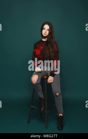 Young brunette teen girl sits on a chair over dark-green background, isolated in studio - Stock Photo