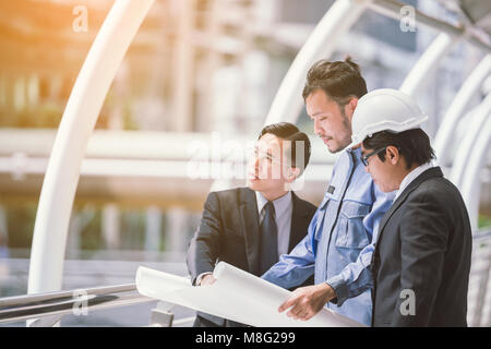 cheerful young engineers discussing the project business of the building looking at blueprint with buildings in - Stock Photo