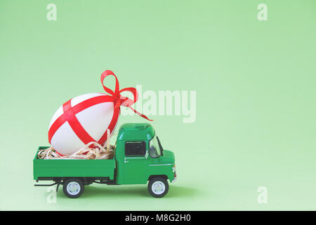 Green pickup toy carrying one decorated easter egg. - Stock Photo
