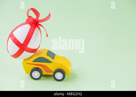 Yellow toy car carrying a decorated easter egg. - Stock Photo
