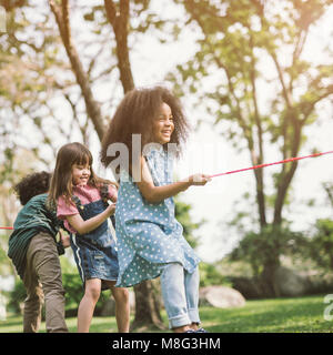 Happy children playing tug of war at the park - Stock Photo