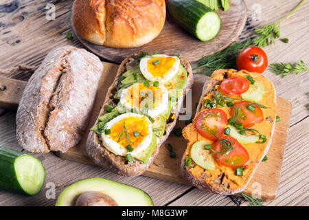 Sandwiches with avocado, eggs and tomato on a wooden background. Fresh organic vegetables, eggs and whole wheat - Stock Photo