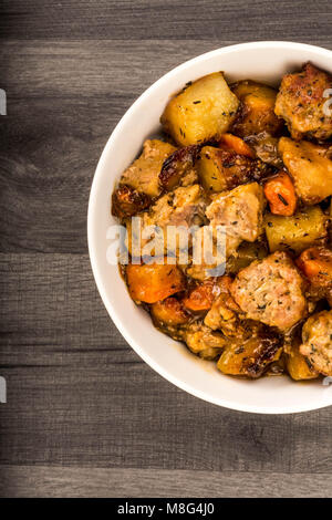 British Or English Style Slow Roasted Pulled Pork And Stuffing Casserole Against A Dark Kitchen Table Top - Stock Photo