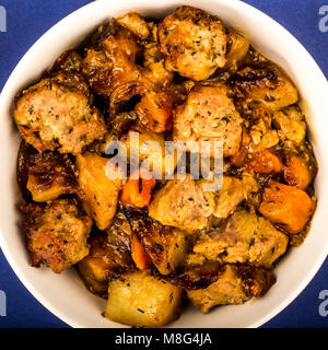 British Or English Style Slow Roasted Pulled Pork And Stuffing Casserole Against A Dark Blue Background