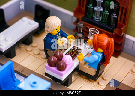 Tambov, Russian Federation - January 04, 2018 Lego couple sitting at the table in Restaurant. Man gets ready to - Stock Photo