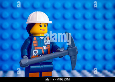 Tambov, Russian Federation - March 09, 2018 Lego miner with pickaxe against blue baseplate background. - Stock Photo