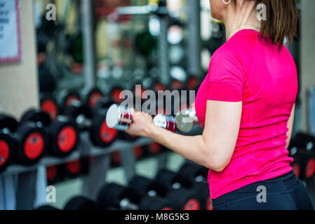 Back view young woman trains biceps in gym - Stock Photo