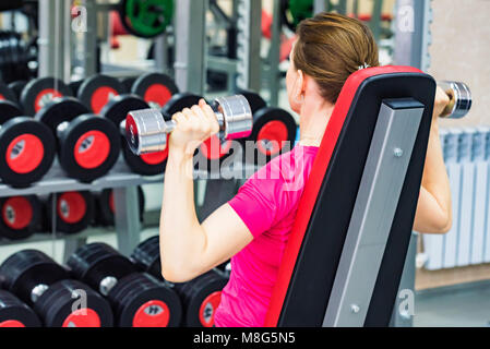 Back view young woman trains deltoid in gym - Stock Photo
