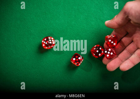Hand rolling red dices on table. - Stock Photo