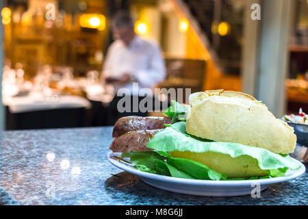A choripan sandwich with lettuce and french white bread on a counter at Mercado Del Puerto, Montevideo, Uruguay. - Stock Photo