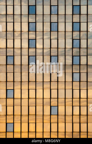 Side of a glass tower building with sky and sun reflecting on its surface - Stock Photo