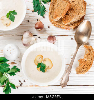Delicious cream soup with mushrooms, parsley and croutons on white wooden table. Selective focus and square image - Stock Photo