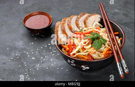 Udon noodles with vegetables (carrots, peppers, zucchini, cucumber, onion, cilantro, garlic), duck and sesame seeds. - Stock Photo