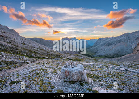 Beautiful painted sky, clouds as the sun comes out from behind the mountains at the horizon. Sunrise in the Dolomites, - Stock Photo