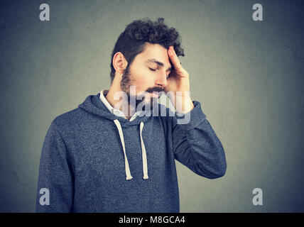 Young casual hipster with beard suffering from misfortune looking tired while rubbing head. - Stock Photo