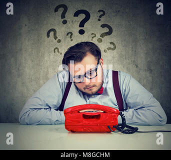 Sad man with too many questions waiting for a call - Stock Photo