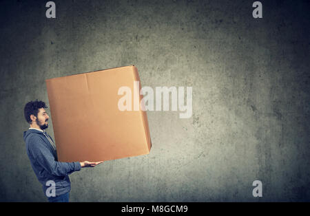 Young man carrying a large box - Stock Photo