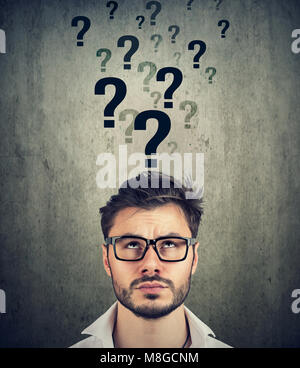 Perplexed man with too many questions and no answer - Stock Photo