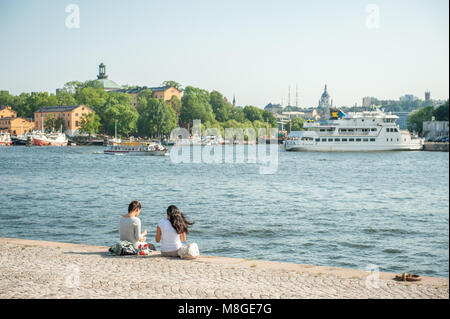 Tourists enjoy a picnic at Nybroviken waterfront in Stockholm. The city is built on 17 islands and can be enjoyed - Stock Photo