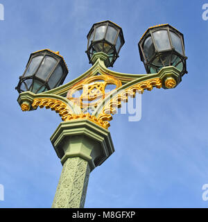 Victorian London ornate cluster of three octagonal lantern street lamps on cast iron column beside pavement on Westminster - Stock Photo