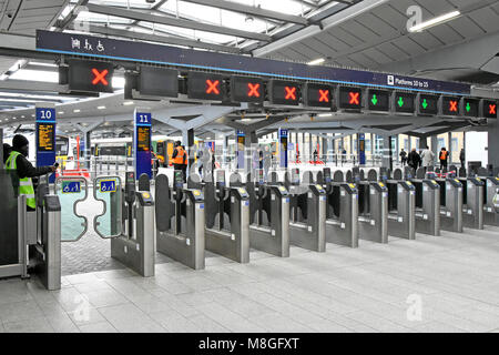 Train station ticket barriers gate across train platform big bold green open red closed access indicator icon sign - Stock Photo