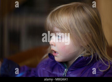 Candid portrait of a young girl with blond hair and blue eyes, wearing a purple jacket. - Stock Photo