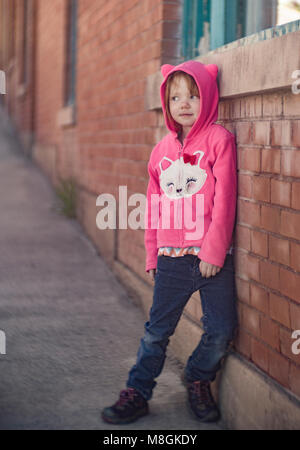 Little red headed girl, leaning against a brick wall, wearing a pink Hello Kitty hoodie.   Canon EOS 6D,  Bausch - Stock Photo