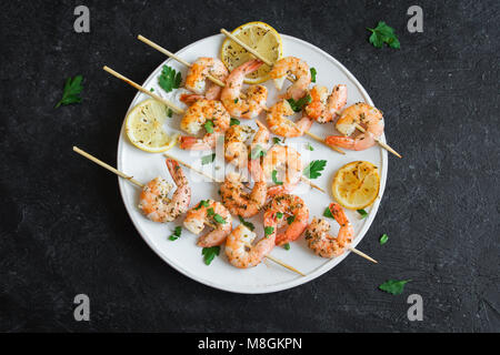 Grilled shrimp skewers. Seafood, shelfish. Shrimps Prawns skewers with spices and fresh herbs on stone black background, - Stock Photo