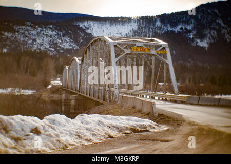 The one lane steel bridge over the Clark Fork River, at Noxon, in Sanders County, Montana. - Stock Photo