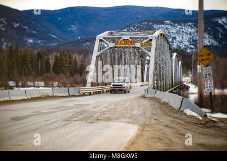 A car crossing the single lane steel bridge over the Clark Fork River, at Noxon, in Sanders County, Montana. - Stock Photo