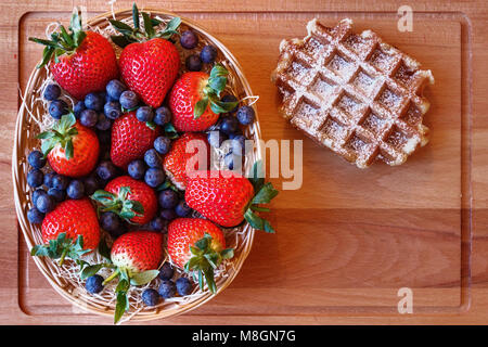A mix of red strawberries with green leaves and blueberries on a hay in a basket on a wooden cutting board with - Stock Photo