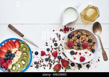 Breakfast bowl of granola and a plate of sliced fruit with seeds, yogurt and honey on a white wood background - Stock Photo