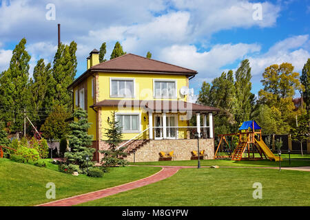 Exterior of beautiful house with green loan and children playground - Stock Photo