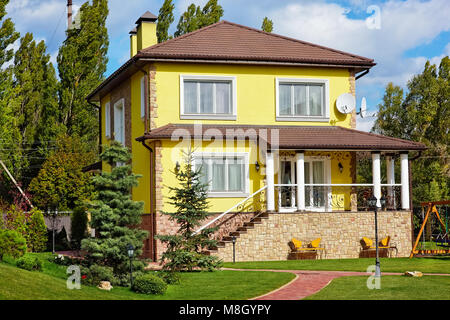 Exterior of beautiful house with green yard and children playground - Stock Photo