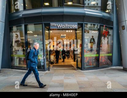 London, UK- Mar 13, 2018: Officer worker walks past a Little Waitrose upmarket supermarket in Walbrook, City of - Stock Photo