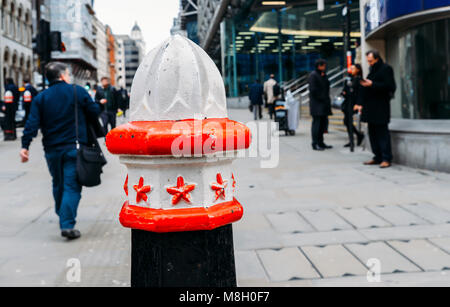 London, UK- Mar 13, 2018: Selective focus on a bollard in the City of London, with City workers in the background - Stock Photo