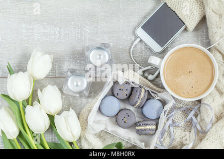 Cup of hot coffee, blue and gray macaroon, white knitting wool, white tulip flowers, mobile phone and headphones, - Stock Photo