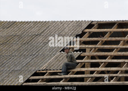 Hands of roofer laying tile on the roof. Installing natural red tile - Stock Photo