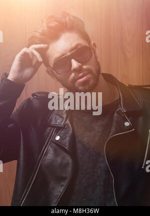Portrait of man in sun glasses. Holding on side of the glasses - Stock Photo