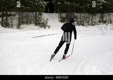 Skier skiing downhill in high mountains during sunny day - Stock Photo