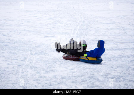 Father and son sledding during winter holiday. Happy dad and little boy playing with snow sled. Man with smiling - Stock Photo