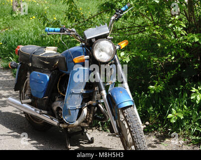 Vintage motorcycle standing in in the rays of sunlight. Side view - Stock Photo