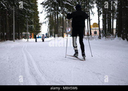 man rides cross-country skiing. Going up the slope with other skiers following - Stock Photo
