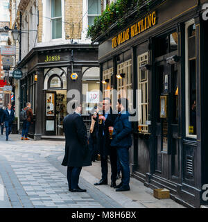Office workers enjoy a pint at lunchtime at the Ye Olde Watling pub in the City of London, England, UK - Stock Photo