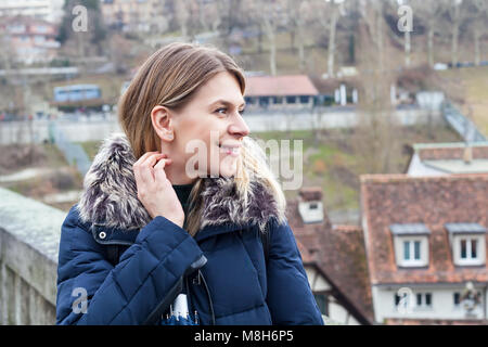 Young female tourist in Bern, Switzerland on a cloudy day exploring the city center - Stock Photo