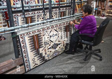 Cameron, AZ, USA: A Navajo woman demonstrates traditional rug weaving at the Cameron Trading Post,  a Native American - Stock Photo