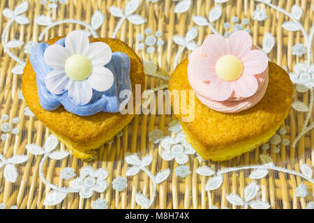 home made heart shaped cupcake cakes, one with strawberry pink frosting icing and one with blue, and rice paper - Stock Photo