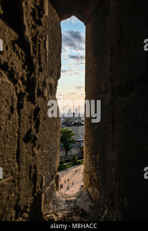 Narrow window in stone wall with view of beautiful Paris cityscape in clouds - Stock Photo