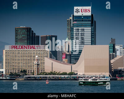 Hong Kong - Star Ferry sails in front of large UBS and Prudential adverts on the Kowloon side of Victoria Harbour - Stock Photo