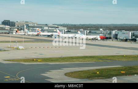 Airplanes of different airliners on tarmac awaiting passengers a - Stock Photo